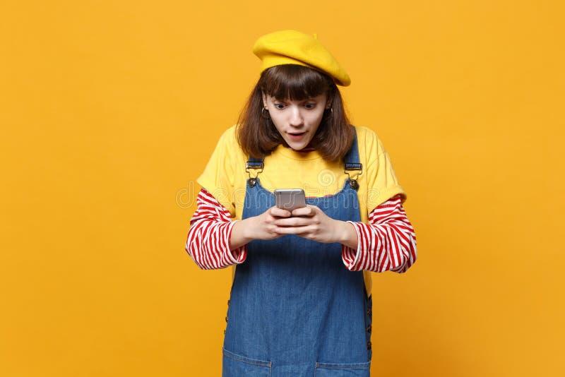 Ο συγκλονισμένος έφηβος κοριτσιών γαλλικό beret, τζιν sundress που χρησιμοποιεί το κινητό τηλέφωνο, δακτυλογραφώντας sms το μήνυμ στοκ φωτογραφίες