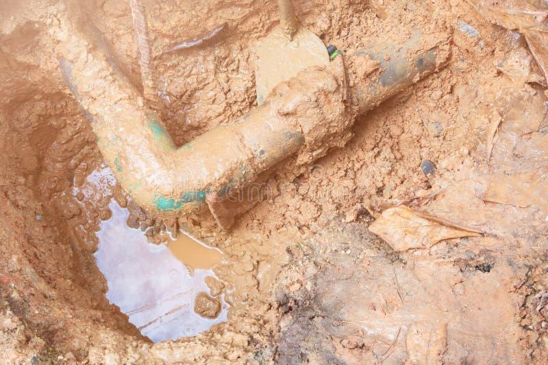Ο σπασμένος σωλήνας στην τρύπα με την κίνηση νερού στην άκρη του δρόμου περιμένει την επισκευή στοκ εικόνες με δικαίωμα ελεύθερης χρήσης