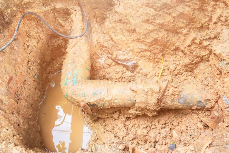 Ο σπασμένος σωλήνας στην τρύπα με την κίνηση νερού στην άκρη του δρόμου περιμένει την επισκευή στοκ εικόνες