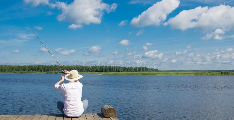Ο ψαράς σε ένα καπέλο, ρίχνει μια ράβδο αλιείας, ενάντια στο νερό και μπλε ουρανός, οπισθοσκόπος, υπάρχει μια θέση για την επιγρα στοκ εικόνες
