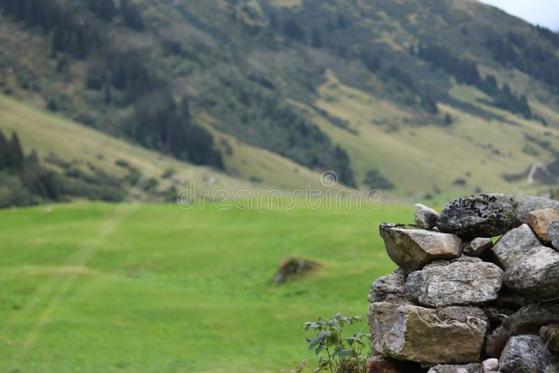 Ο τοίχος πετρών στο πρώτο πλάνο και μια όμορφη πανοραμική άποψη των βουνών στοκ εικόνες με δικαίωμα ελεύθερης χρήσης