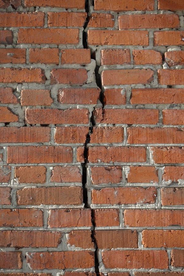 Ο τούβλινος τοίχος διαιρείται με μια κάθετη ρωγμή Έννοια χωρισμού στοκ φωτογραφία με δικαίωμα ελεύθερης χρήσης