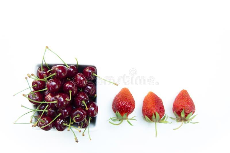 Ο τοπ πυροβολισμός, κλείνει επάνω των φρέσκων γλυκών κερασιών με τις πτώσεις νερού στο άσπρες κύπελλο και τις φράουλες που απομον στοκ εικόνα