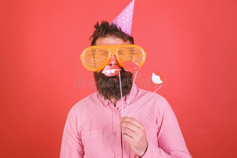 Ο τύπος στο καπέλο κομμάτων γιορτάζει, θέτοντας με τα στηρίγματα φωτογραφιών Συναισθηματική έννοια ποικιλομορφίας Το άτομο με τη  στοκ φωτογραφία με δικαίωμα ελεύθερης χρήσης