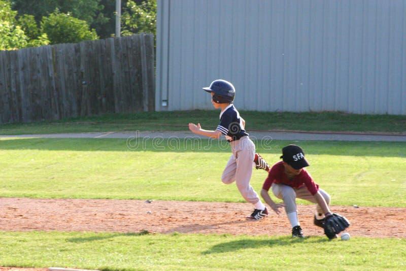 Ο φορέας σόφτμπολ μικρού πρωταθλήματος ορμά για το παίχτη τρίτης βάσης ενώ ο παίχτης δεύτερης βάσης φθάνει για τη σφαίρα στοκ εικόνα