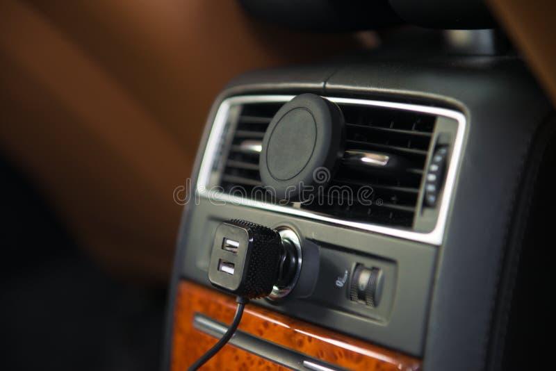 Ο φορτιστής USB και ο κινητός τηλεφωνικός κάτοχος μαγνητών A/$l*c τοποθετούν στο οπίσθιο κάθισμα αυτοκινήτων πολυτέλειας στοκ εικόνες