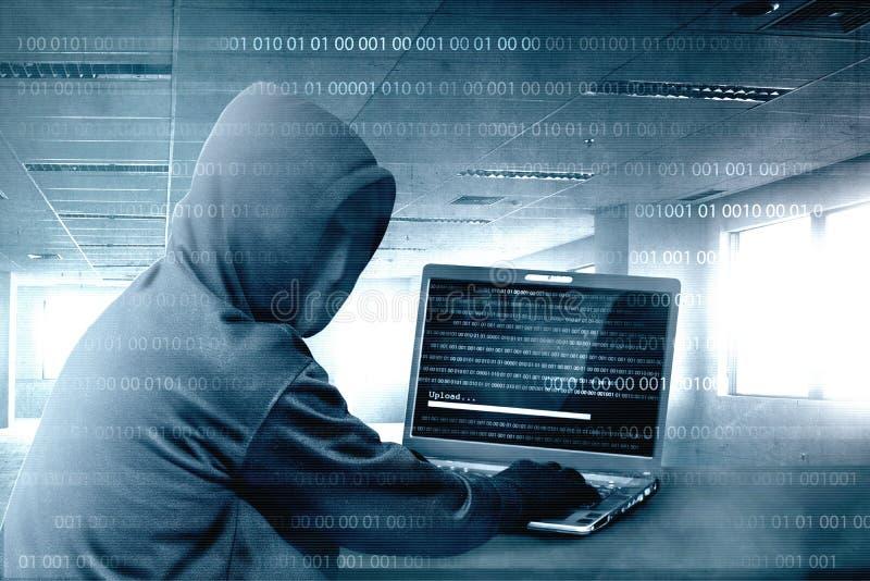 Ο χάκερ στο μαύρο hoodie που χρησιμοποιεί το lap-top στο γραφείο στη χάραξη του συστήματος με το δυαδικό κώδικα και φορτώνει το m απεικόνιση αποθεμάτων