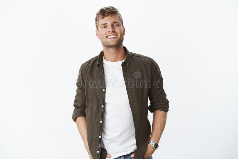 Ο χαλαρωμένος, φιλικός όμορφος ευρωπαϊκός τύπος με τη σκληρή τρίχα που χαμογελά χαρωπά με το άσπρο υγιές κράτημα δοντιών παραδίδε στοκ φωτογραφίες με δικαίωμα ελεύθερης χρήσης