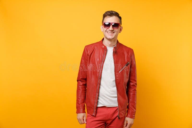 Ο χαριτωμένος όμορφος νεαρός άνδρας μόδας πορτρέτου 25-30 έτη στο κόκκινο σακάκι δέρματος, γυαλιά ηλίου μπλουζών απομόνωσε στη φω στοκ φωτογραφίες με δικαίωμα ελεύθερης χρήσης