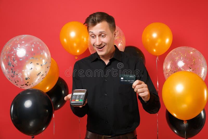 Ο χαρούμενος νεαρός άνδρας που κρατά το ασύρματο σύγχρονο τερματικό πληρωμής τραπεζών στη διαδικασία, αποκτά τη μαύρη κάρτα πληρω στοκ εικόνες