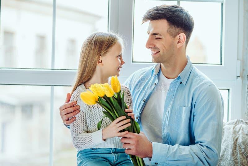 Ο χρόνος με τον μπαμπά είναι πάντα μεγάλος Ο πατέρας δίνει στην κόρη της μια ανθοδέσμη των τουλιπών στοκ εικόνες