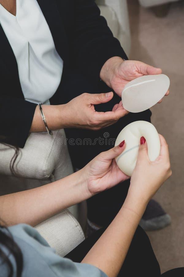 Ο πλαστικοί χειρούργος και ο ασθενής συζητούν την επιλογή των μοσχευμάτων στηθών μετά από τη μαστεκτομή ή για την αύξηση στηθών στοκ φωτογραφία