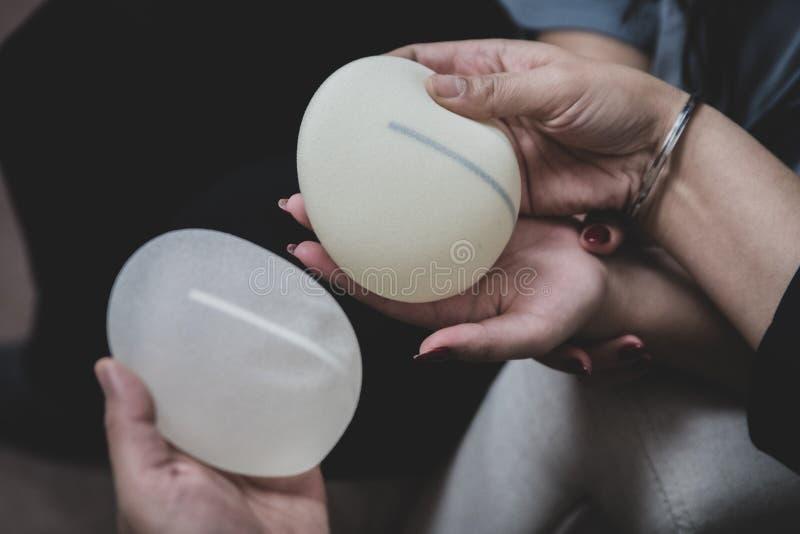 Ο πλαστικοί χειρούργος και ο ασθενής συζητούν την επιλογή των μοσχευμάτων στηθών μετά από τη μαστεκτομή ή για την αύξηση στηθών στοκ εικόνες