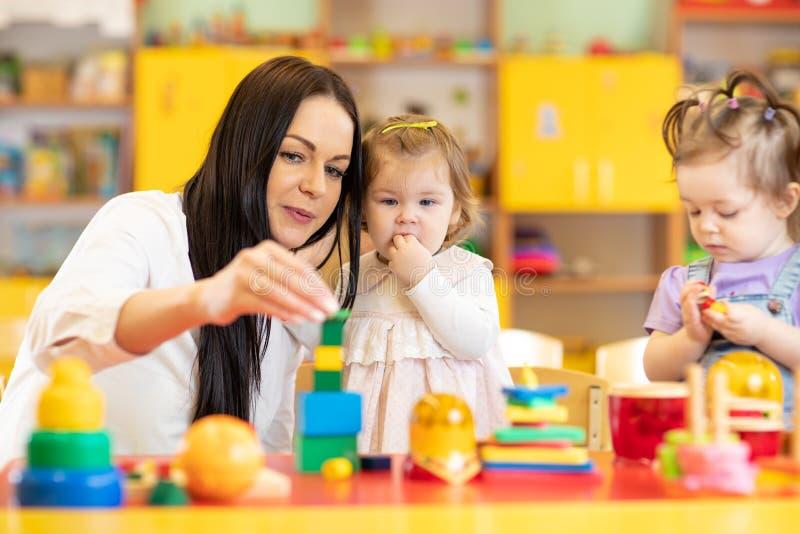Δάσκαλος βρεφικών σταθμών που φροντίζει τα παιδιά στη φύλαξη Τα μικρά παιδιά παιδάκι παίζουν μαζί με τα αναπτυξιακά παιχνίδια στοκ εικόνες με δικαίωμα ελεύθερης χρήσης