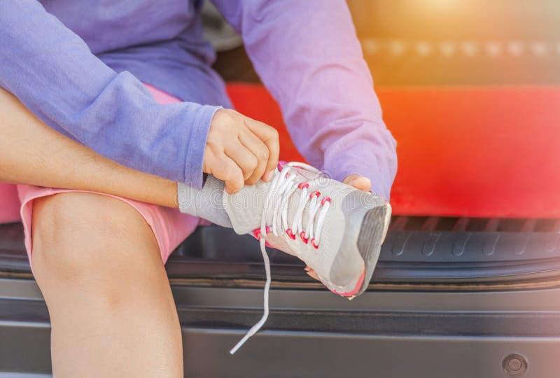 Δένοντας κορδόνια συνεδρίασης γυναικών πρίν εκπαιδεύει την καρδιο άσκηση workout στοκ φωτογραφία με δικαίωμα ελεύθερης χρήσης