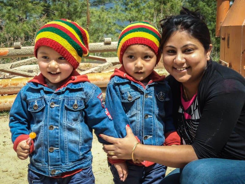 Δίδυμα Bhutanese παιδιά στη ζωηρόχρωμη τοποθέτηση ένδυσης για μια φωτογραφία με μια κυρία στοκ εικόνες