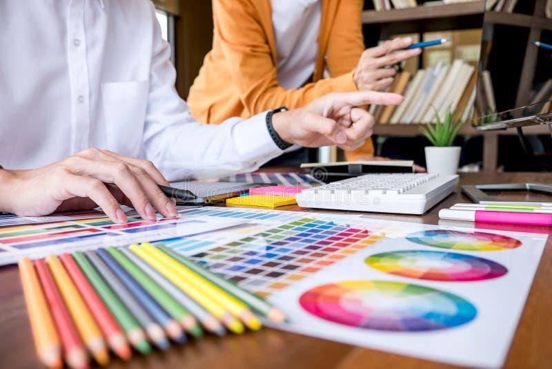 Δημιουργικός γραφικός σχεδιαστής δύο συναδέλφων που εργάζεται στην επιλογή χρώματος και που επισύρει την προσοχή στην ταμπλέτα γρ στοκ εικόνες