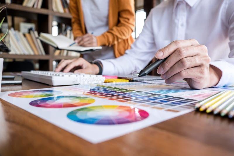 Δημιουργικός γραφικός σχεδιαστής δύο συναδέλφων που εργάζεται στην επιλογή χρώματος και που επισύρει την προσοχή στην ταμπλέτα γρ στοκ φωτογραφία