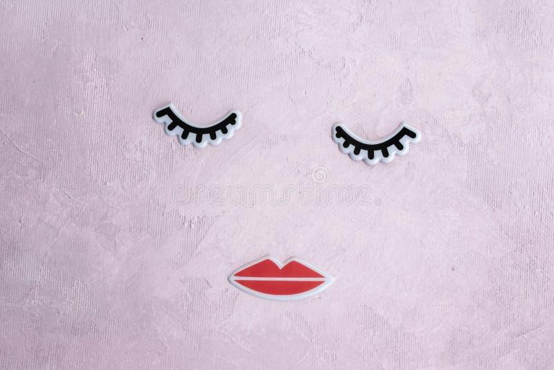 Δημιουργικό πρόσωπο γυναικών φιαγμένο από eyelashes, και χείλια Ελάχιστη έννοια ομορφιάς Το ρόδινο υπόβαθρο, διαμορφώνει το επίπε στοκ εικόνες