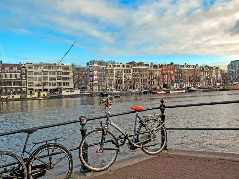 Διάσημα ολλανδικά παραδοσιακά φλαμανδικά κτήρια τούβλου ποδηλάτων και του Άμστερνταμ στο κανάλι στοκ εικόνες