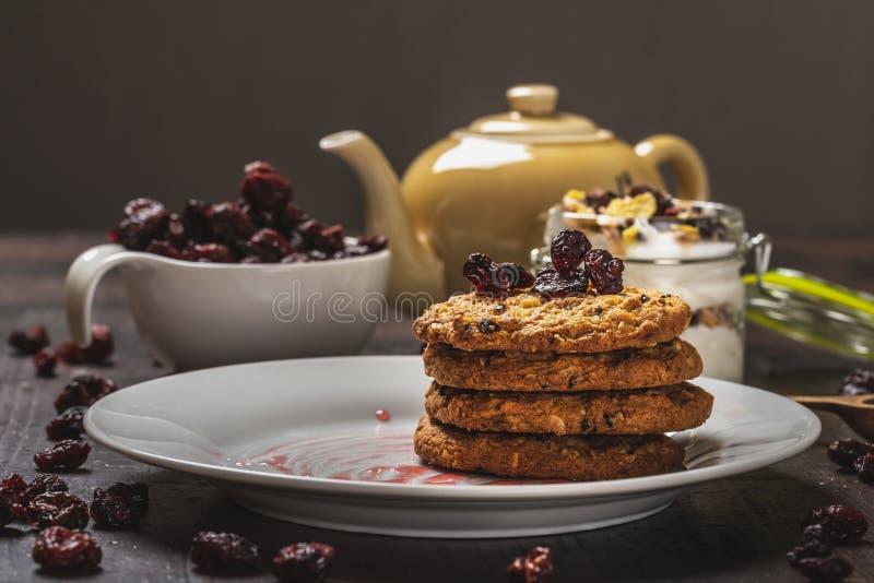 Διάφορα μπισκότα στο άσπρο πιάτο με τα ξηρά μούρα στο σκοτεινό ξύλινο πίνακα στοκ φωτογραφίες