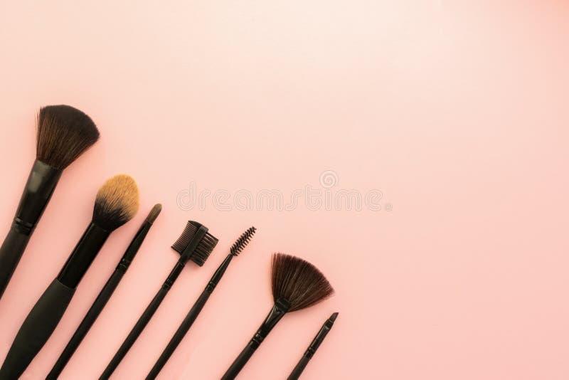 Διάφορες μικρές βούρτσες μικρές για την εφαρμογή του διακοσμητικού makeup σε ένα λεπτό ρόδινο υπόβαθρο Έννοια προσοχής και ομορφι στοκ εικόνα