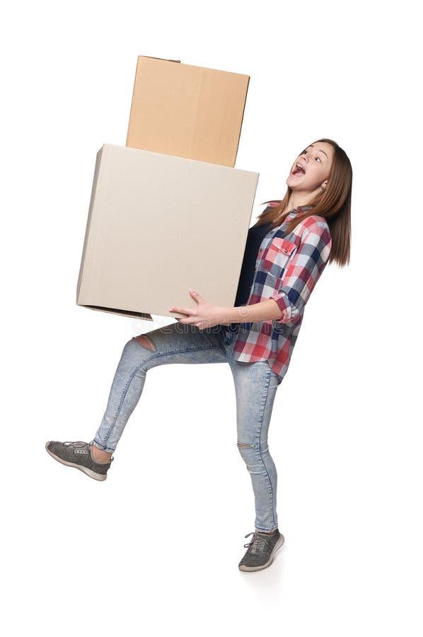 Διέγερση του νέου θηλυκού που φέρνει τα βαριά κουτιά από χαρτόνι που τείνουν να πέσει στοκ φωτογραφία με δικαίωμα ελεύθερης χρήσης