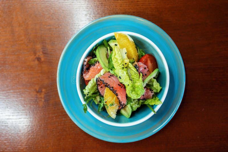 Διαιτητική σαλάτα με τη λωρίδα σολομών με τις φέτες ντοματών με το μαρούλι και πράσινα σε ένα μπλε πιάτο σε ένα εστιατόριο Χρήσιμ στοκ φωτογραφίες με δικαίωμα ελεύθερης χρήσης
