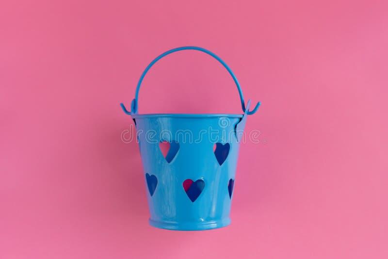 Διακοσμητικός μπλε κάδος με διαμορφωμένες τις καρδιά τρύπες στο ρόδινο υπόβαθρο Εορταστική έννοια στοκ εικόνες