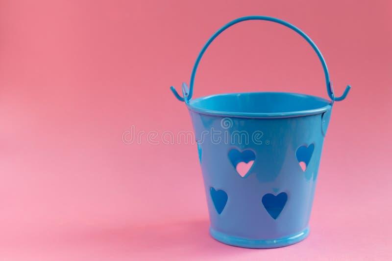 Διακοσμητικός μπλε κάδος με διαμορφωμένες τις καρδιά τρύπες στο ρόδινο υπόβαθρο Εορταστική έννοια στοκ εικόνα με δικαίωμα ελεύθερης χρήσης