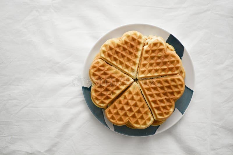 Διαμορφωμένη καρδιά βάφλα σε ένα πιάτο πρόγευμα πρωινού ή επιδόρπιο απογεύματος με το τσάι στοκ φωτογραφία