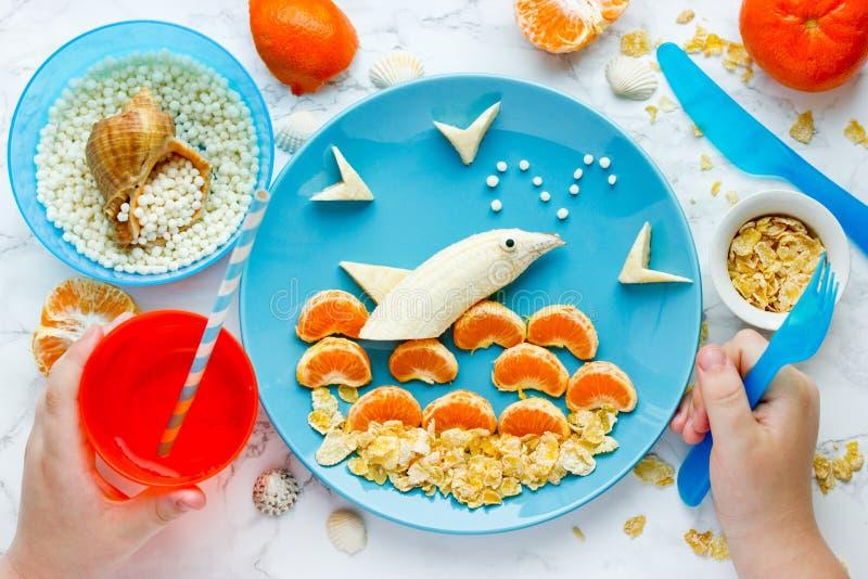 Διασκέδαση και υγιή τρόφιμα για το δελφίνι φρούτων παιδιών στοκ εικόνες