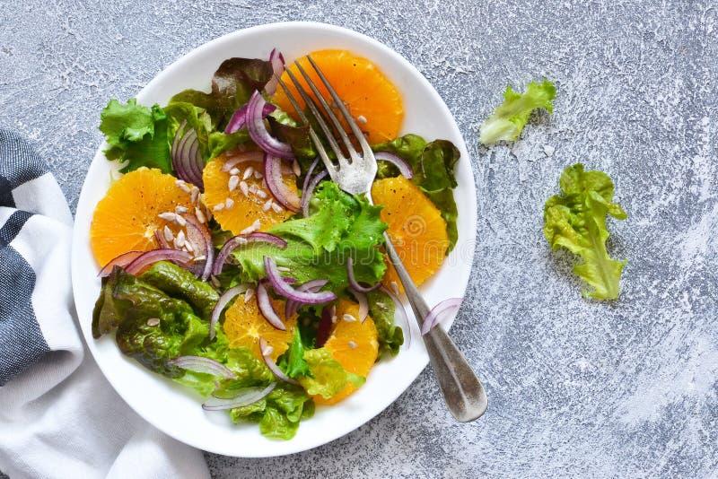 Διατροφή Detox Σαλάτα με το πορτοκάλι, το κρεμμύδι και τους σπόρους στον πίνακα κουζινών στοκ φωτογραφία
