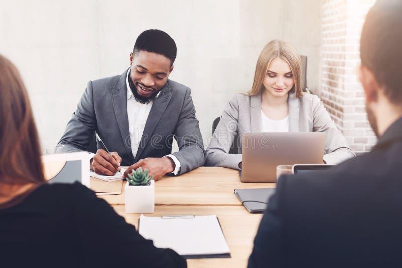 Διαφορετική εργασία επιχειρηματιών μαζί στην αρχή στοκ εικόνα