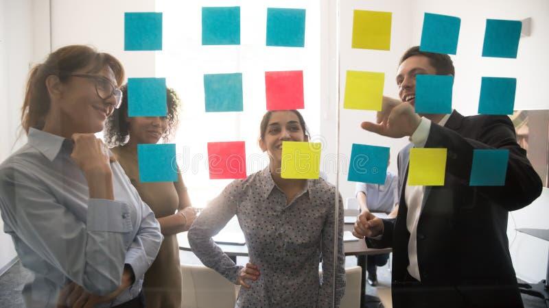 Διαφορετικοί άνθρωποι ομάδων που εξετάζουν τις κολλώδεις σημειώσεις για το 'brainstorming' γυαλιού στοκ εικόνα