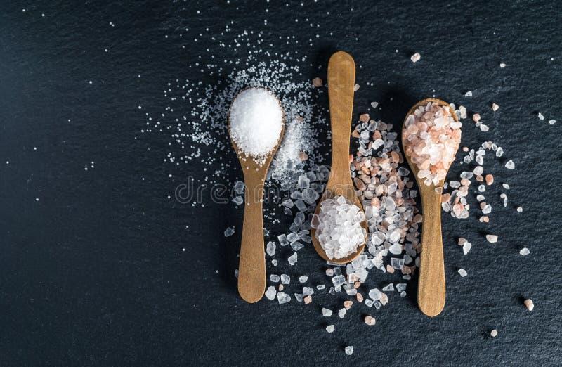 Διαφορετικοί τύποι αλάτων Τοπ άποψη σχετικά με τρία ξύλινα κουτάλια στοκ εικόνες με δικαίωμα ελεύθερης χρήσης