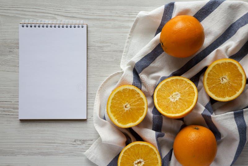 Διχοτομημένα και ολόκληρα πορτοκάλια, κενό σημειωματάριο, τοπ άποψη Υπερυψωμένος, άνωθεν, επίπεδος βάζει Διάστημα για το κείμενο στοκ εικόνα