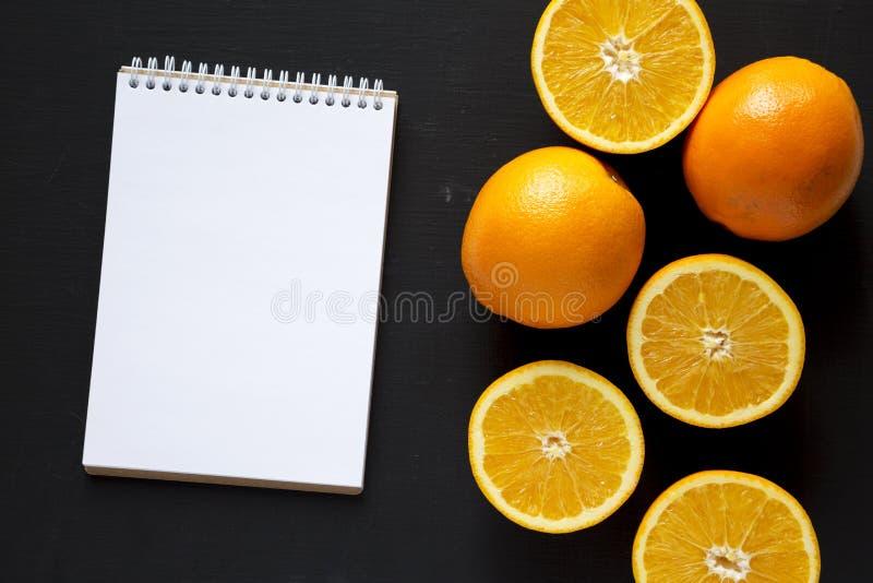 Διχοτομημένα και ολόκληρα πορτοκάλια, κενό σημειωματάριο πέρα από το μαύρο υπόβαθρο, υπερυψωμένη άποψη Η τοπ άποψη, άνωθεν, επίπε στοκ εικόνες