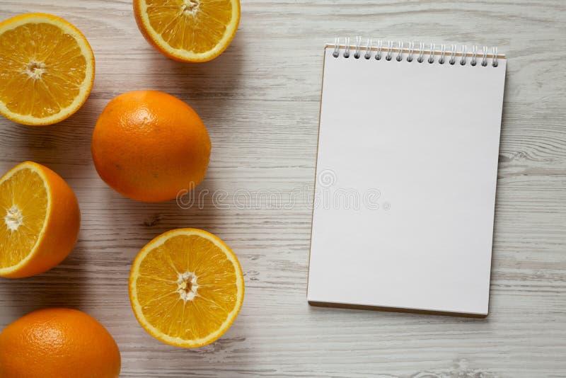 Διχοτομημένα και ολόκληρα πορτοκάλια με το κενό σημειωματάριο πέρα από το άσπρο ξύλινο υπόβαθρο, υπερυψωμένη άποψη Η τοπ άποψη, ά στοκ εικόνες με δικαίωμα ελεύθερης χρήσης