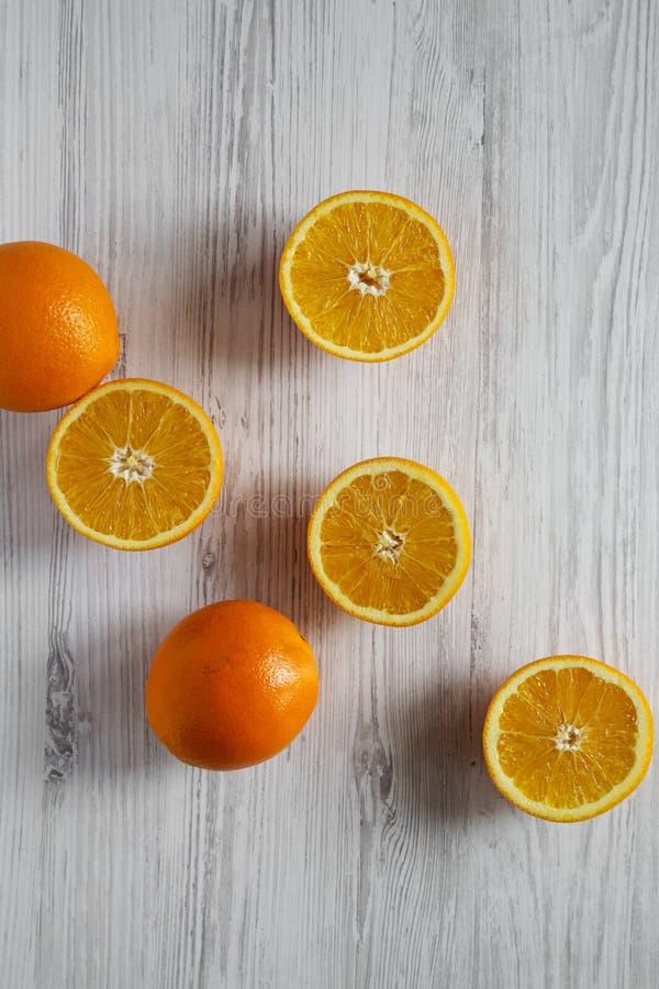 Διχοτομημένα και ολόκληρα πορτοκάλια στον άσπρο ξύλινο πίνακα, τοπ άποψη Υπερυψωμένος, άνωθεν, επίπεδος βάζει στοκ φωτογραφία με δικαίωμα ελεύθερης χρήσης