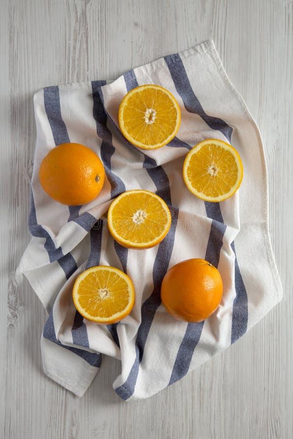 Διχοτομημένα και ολόκληρα πορτοκάλια στον άσπρο ξύλινο πίνακα, τοπ άποψη Υπερυψωμένος, άνωθεν, επίπεδος βάζει στοκ φωτογραφίες με δικαίωμα ελεύθερης χρήσης