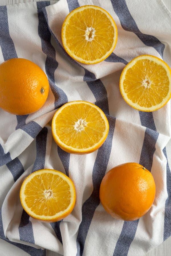 Διχοτομημένα και ολόκληρα πορτοκάλια στο ύφασμα, τοπ άποψη Υπερυψωμένος, άνωθεν, επίπεδος βάζει Κινηματογράφηση σε πρώτο πλάνο στοκ εικόνες με δικαίωμα ελεύθερης χρήσης