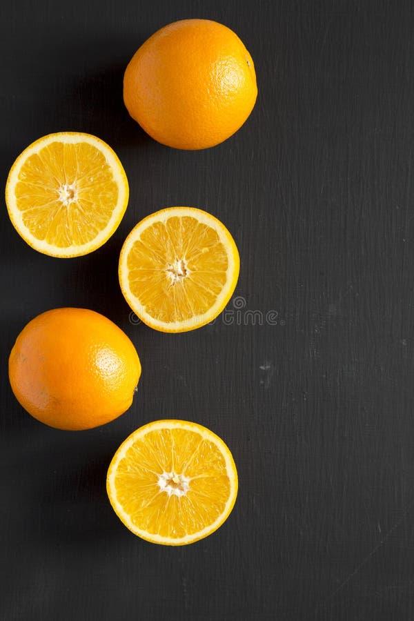 Διχοτομημένα και ολόκληρα πορτοκάλια πέρα από τη μαύρη επιφάνεια, τοπ άποψη Υπερυψωμένος, άνωθεν, επίπεδος βάζει διάστημα αντιγρά στοκ φωτογραφία