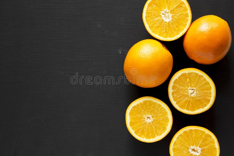 Διχοτομημένα και ολόκληρα πορτοκάλια πέρα από το μαύρο υπόβαθρο, τοπ άποψη Υπερυψωμένος, άνωθεν, επίπεδος βάζει Διάστημα για το κ στοκ φωτογραφίες