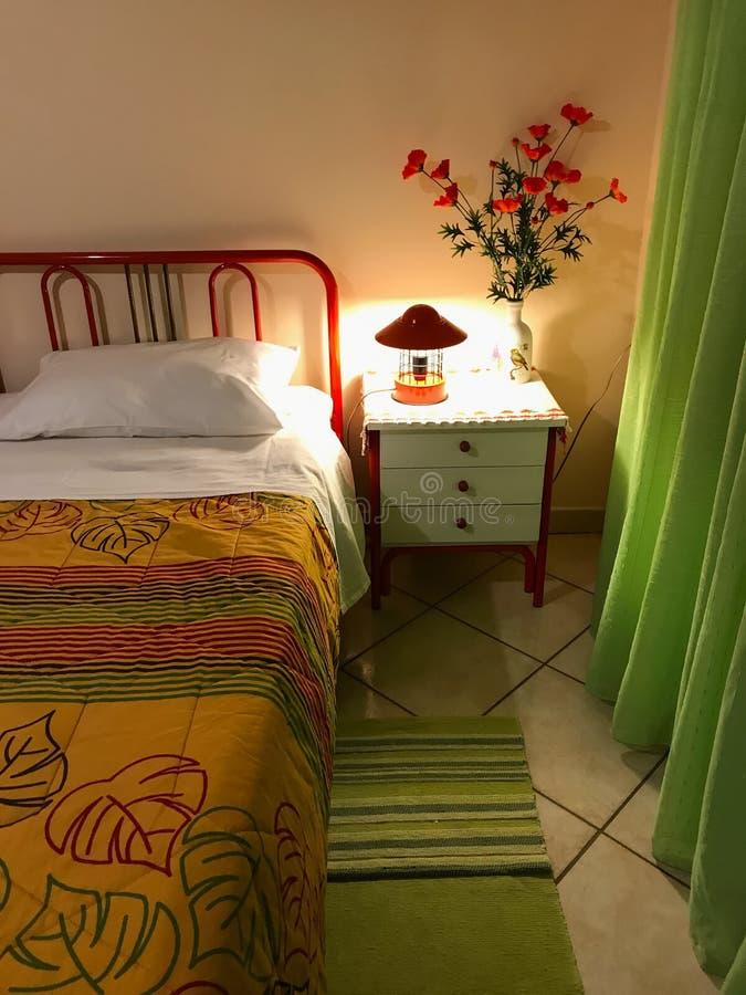 Δονούμενο χρωματισμένο εσωτερικό μιας κρεβατοκάμαρας Μαξιλάρι και ζωηρόχρωμο coverlet στο κρεβάτι Εσωτερικό σχέδιο κρεβατοκάμαρων στοκ εικόνες