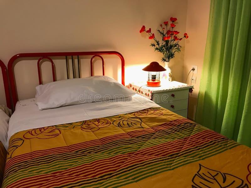 Δονούμενο χρωματισμένο εσωτερικό μιας κρεβατοκάμαρας Μαξιλάρι και ζωηρόχρωμο coverlet στο κρεβάτι Εσωτερικό σχέδιο κρεβατοκάμαρων στοκ φωτογραφία