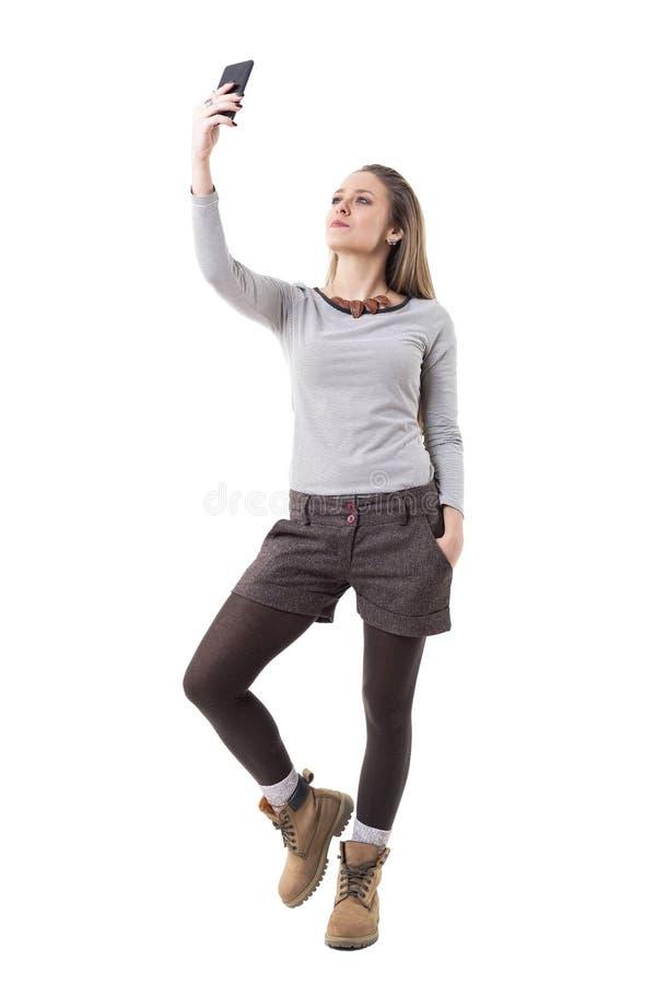 Δροσερή βέβαια νέα μοντέρνη γυναίκα με το κινητό τηλέφωνο που παίρνει την αυτοπροσωπογραφία στοκ φωτογραφία