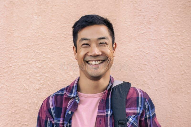 Δροσερό ευτυχές άτομο που στέκεται έξω ενάντια στον τοίχο στοκ εικόνες