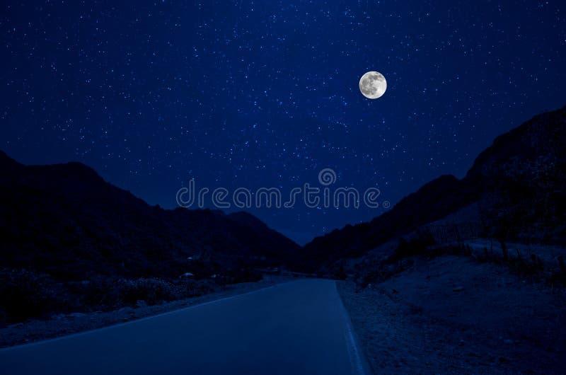 Δρόμος βουνών μέσω του δάσους σε μια νύχτα πανσελήνων Φυσικό τοπίο νύχτας του σκούρο μπλε ουρανού με το φεγγάρι φλυάρων στοκ εικόνα