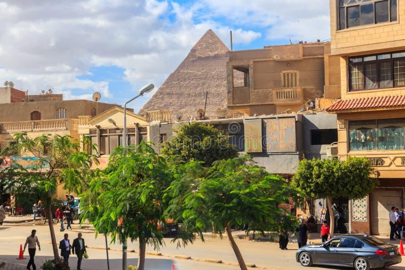 Δρόμος με έντονη κίνηση στο Κάιρο με την κορυφή της πυραμίδας Khafre πίσω από τα σπίτια στοκ φωτογραφίες